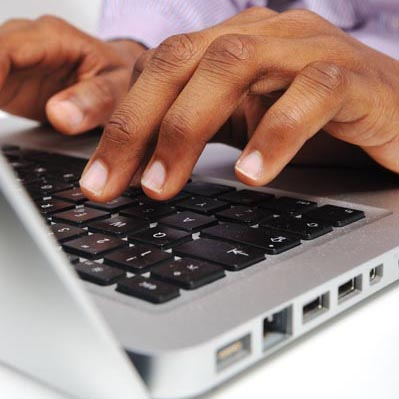 Image of someone entering data on a laptop