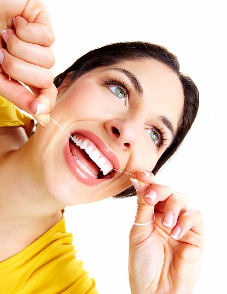 Image of woman smiling while she is flossing her teeth