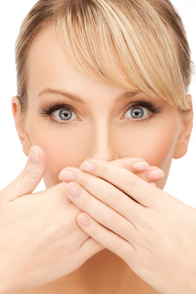 Image of woman covering her mouth to high crooked teeth