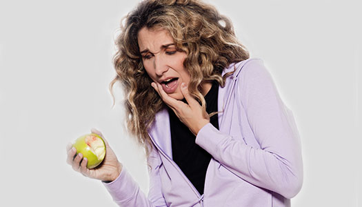 image of a woman with bleeding gums trying to eat an apple