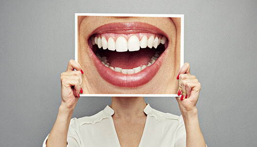 image of a woman with hiding crooked smile with a photo of straight teeth